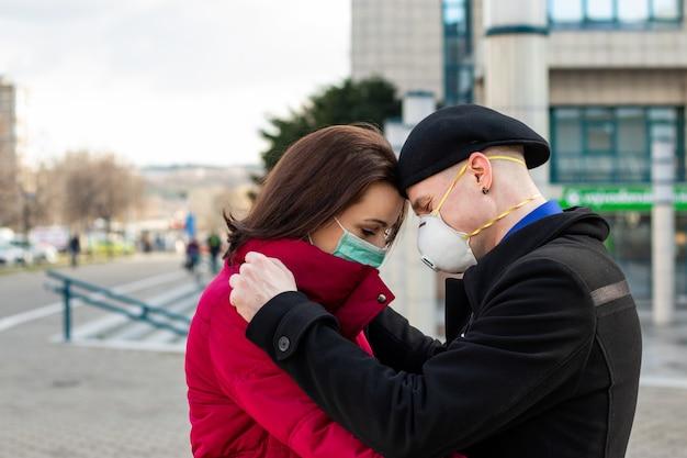 Man en vrouw praten nauw met elkaar op straat terwijl ze voor de zekerheid chirurgische maskers dragen