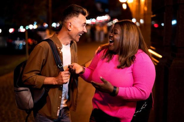 Man en vrouw praten 's nachts in de stadslichten