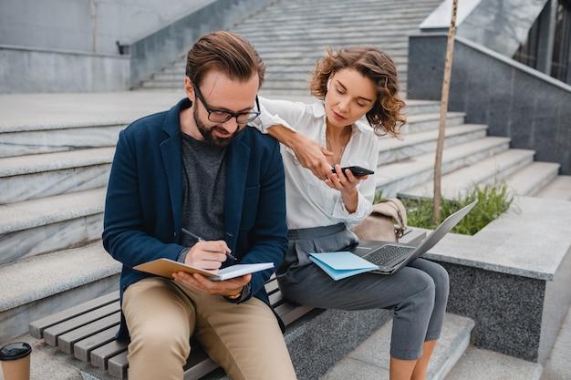 Man en vrouw praten zittend op trappen in stedelijk stadscentrum