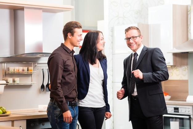 Man en vrouw raadplegen verkoper voor binnenlandse keuken in studio of meubelwinkel