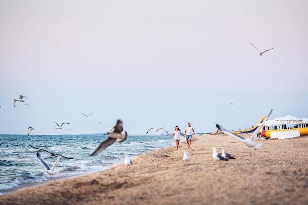 Man en vrouw rennen langs de kustlijn en jagen zeevogels weg.