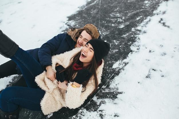 Man en vrouw rijden op het ijs op een bevroren meer