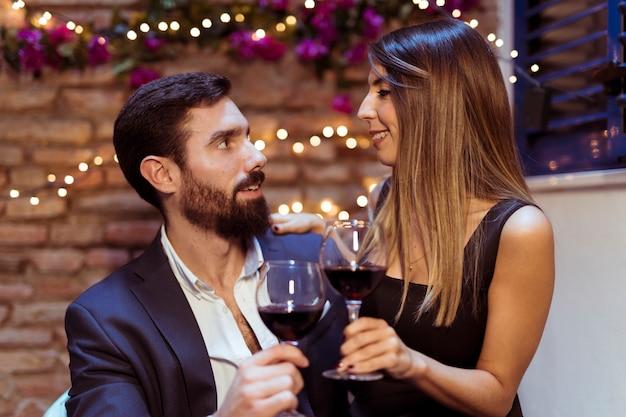 Man en vrouw rinkelende glazen drinken