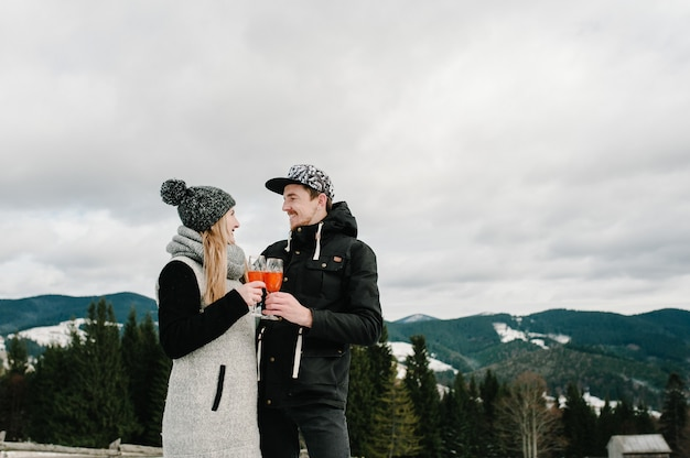 Man en vrouw roosteren met glazen champagne op de picknick van de winternacht op de berg.