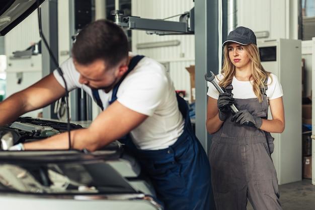 Man en vrouw samen auto repareren