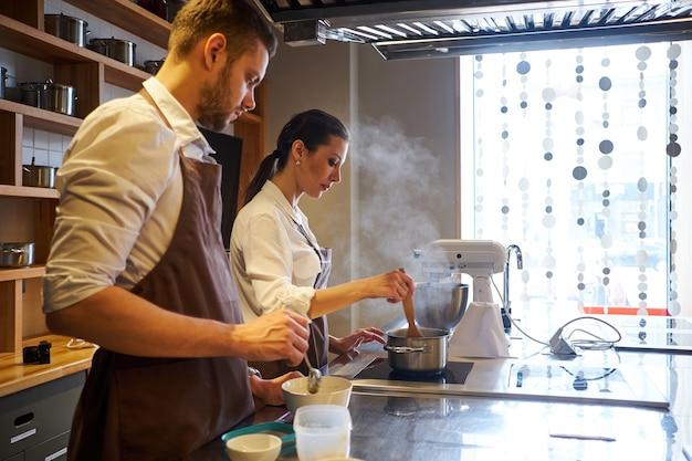 Man en vrouw samen koken in de keuken van bakkerij. beroep bereiding zoetwaren.