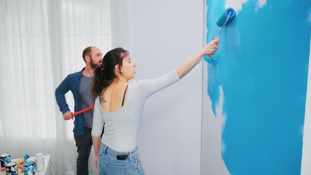 Man en vrouw schilderen muur tijdens huisrenovatie met rolborstel. woondecoratie en renovatie in een gezellig appartement, reparatie en make-over