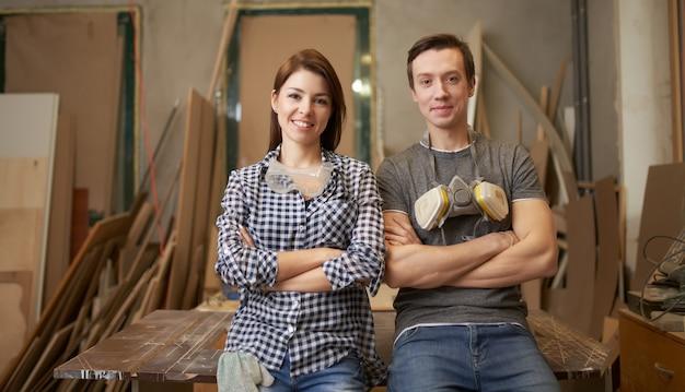 Man en vrouw schrijnwerkers met gekruiste armen in werkplaats