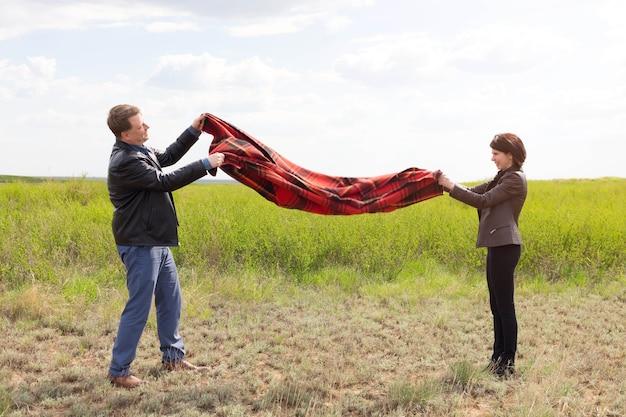Man en vrouw schudden stof en vuil van een deken tijdens een picknick.