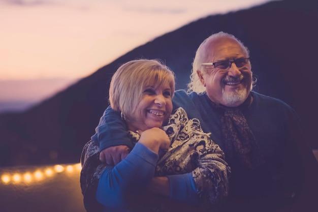 Man en vrouw senior heren oud verliefd knuffelen en veel plezier lachend op het dak in vakantie thuis. nachtlichtatmosfeer voor romantische scène. samen voor altijd concept en glimlacht