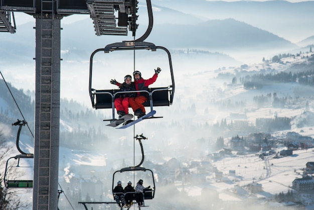 Man en vrouw snowboarders op kabelskilift