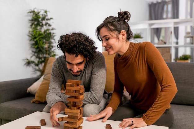 Man en vrouw spelen een houten torenspel