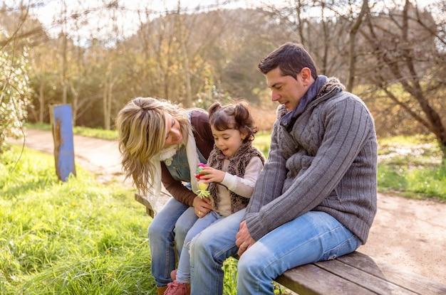 Man en vrouw spelen met een klein meisje zittend op het midden van een houten bankje in het park. familie vrije tijd buitenshuis concept.