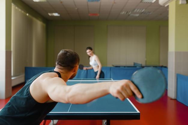 Man en vrouw spelen pingpong binnenshuis, focus op racket. paar in sportkleding speelt tafeltennis in sportschool