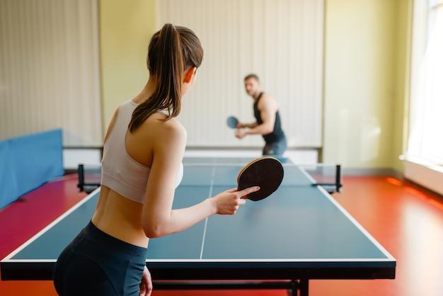 Man en vrouw spelen pingpong binnenshuis