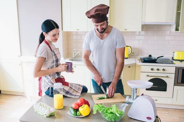 Man en vrouw staan in de keuken. man snijdt komkommer.