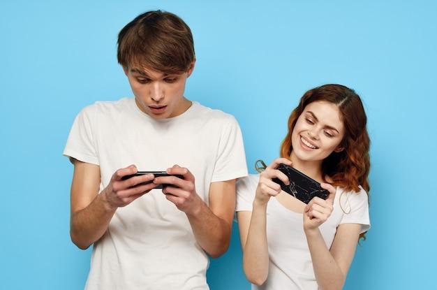 Man en vrouw staan naast de telefoon in handen communicatietechnologie blauwe achtergrond