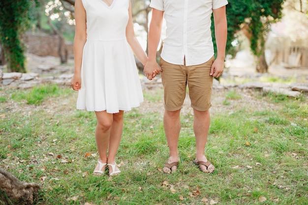 Man en vrouw staan naast elkaar in het park op het gras en houden elkaars hand vast