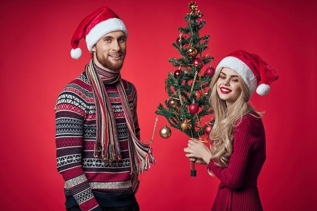 Man en vrouw staan naast kerstboom speelgoed levensstijl rode achtergrond. hoge kwaliteit foto