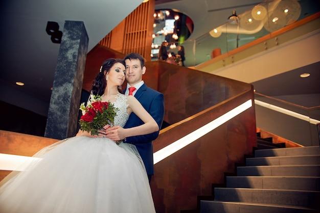 Man en vrouw staan op de trap en knuffelen. mooie witte jurk op het lichaam van de vrouw, een boeket rozen in de handen van het meisje