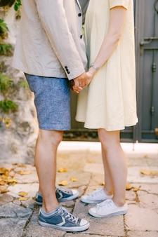 Man en vrouw staan op straat hand in hand close-up