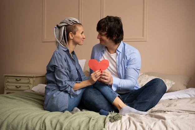 Man en vrouw thuis op bed met rood hartvalentijnskaart in handen.