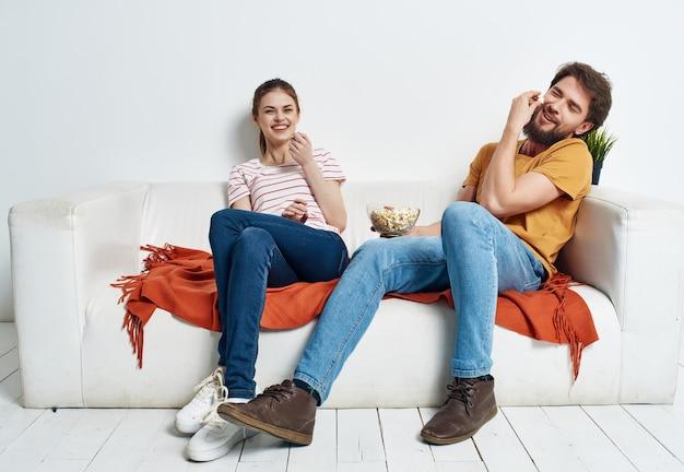 Man en vrouw thuis op de bank met popcorn films kijken ontspannend
