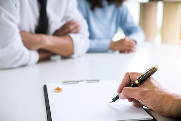 Man en vrouw tijdens echtscheidingsproces met advocaat of consulent en ondertekening van echtscheiding co