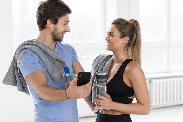 Man en vrouw tijdens een training in de sportschool. guy toont aan zijn teamgenoot een nieuwe fitness-applicatie op de smartphone.