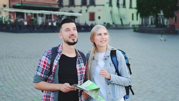Man en vrouw toeristen met kaart op zoek naar nieuwe historische plek in het stadscentrum