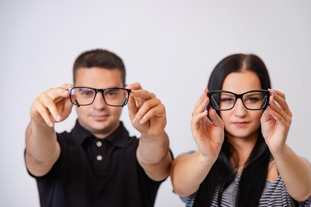 Man en vrouw tonen moderne brillen met zwarte randen