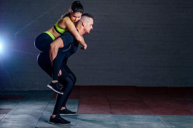 Man en vrouw trainen samen in de sportschool op een achtergrond van zwarte bakstenen. coöperatieve sit-ups