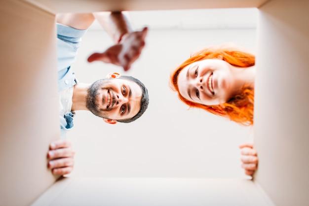 Man en vrouw, uitzicht vanuit de kartonnen doos