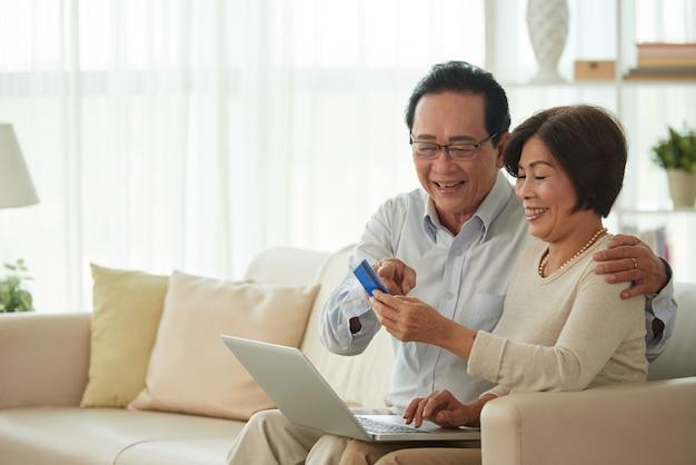 Man en vrouw van middelbare leeftijd die online winkelen
