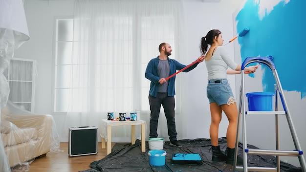 Man en vrouw veranderen de muurkleur met behulp van een rolborstel tijdens de renovatie van een huis. woondecoratie en renovatie in een gezellig appartement, reparatie en make-over