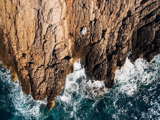 Man en vrouw verliefd liggend omhelst en op het bovenaanzicht van de rotsachtige kust