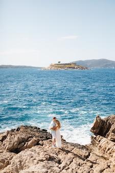 Man en vrouw verliefd staan elkaar omhelzend op de rotsachtige kust achter hen is de