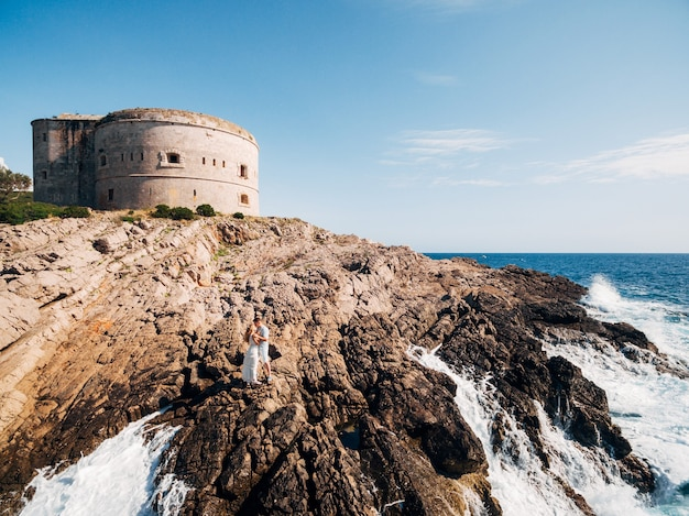 Man en vrouw verliefd staan omarmen en hand in hand op de rotsachtige kust in de buurt van het fort van arza
