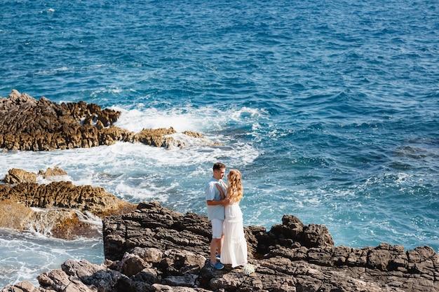 Man en vrouw verliefd staan omarmen en hand in hand op de rotsachtige kust