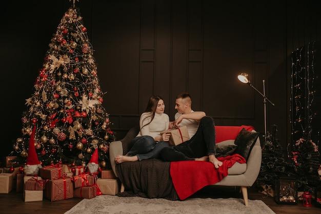 Man en vrouw verliefde paar openen geschenkdozen, maken een boog los bij de kerstboom