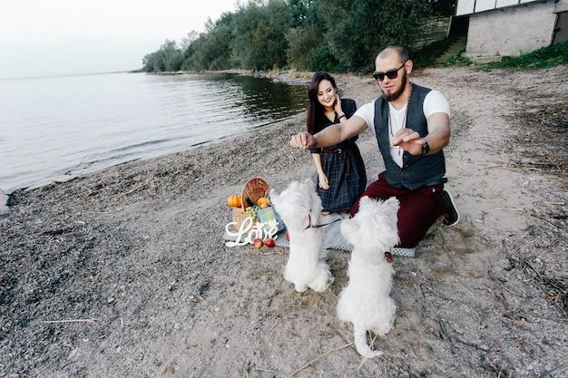 Man en vrouw vermaken zich prima op het strand met hun twee witte pups