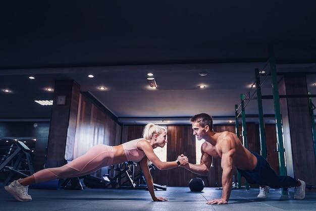 Man en vrouw versterken handen bij fitnesstraining. fitness jongeren doen push-ups in een sportschool op zoek naar gezicht gelukkige oefening