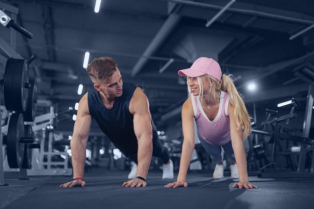 Man en vrouw versterken handen bij fitnesstraining. geschiktheidsjongeren die opdrukoefeningen in een gymnastiek doen die gezichts gelukkige oefening kijken
