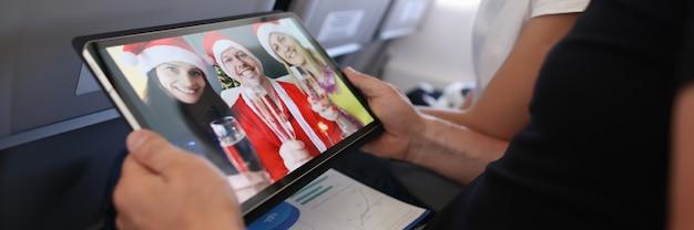 Man en vrouw vieren kerst met vrienden in santa claus hoeden via scherm op digitale tafel...