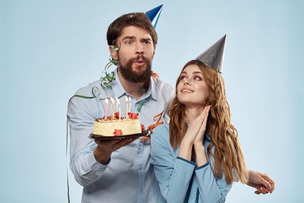 Man en vrouw vieren verjaardag met cake en in hoeden op blauw.