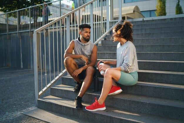 Man en vrouw vrienden zittend op trappen buiten in de stad, praten na het sporten.