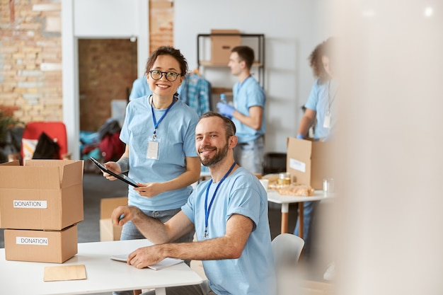 Man en vrouw vrijwilligers glimlachen naar de camera en werken graag samen aan een donatieproject binnenshuis, ze