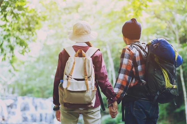 Man en vrouw wandelen bij zonsondergang bergen met zware rugzak travel lifestyle reislust avontuur concept zomervakanties buiten alleen in het wild