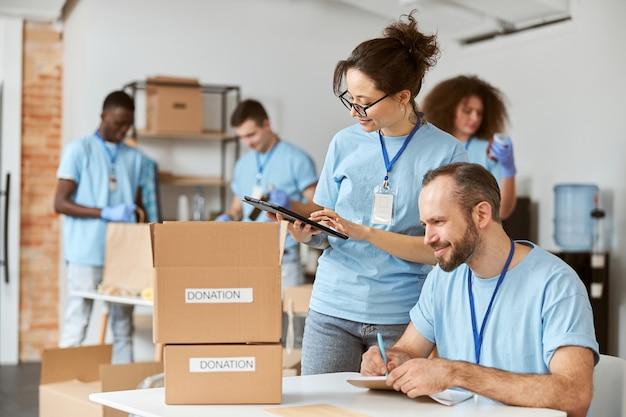 Man en vrouw werken graag samen aan een donatieproject binnenshuis team van vrijwilligers in blauw uniform