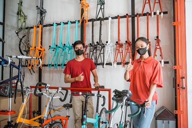 Man en vrouw werknemer in zwart masker met duimen omhoog bij het vasthouden en voorbereiden van fietsen